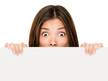 Banner sign woman peeking over edge of blank empty paper billboard with copy space for text. Beautiful Asian Caucasian woman looking surprised and scared - funny. Isolated on white background.