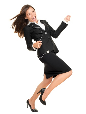 earbud: Woman listening to music on mp3 player, dancing playing air guitar. Funny happy portrait of business woman isolated on white background in full length.