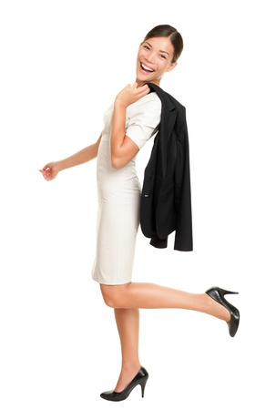 Walking business woman smiling happy  isolated on white background in full length holding her jacket casual over the shoulder. Mixed race Caucasian Asian businesswoman. photo