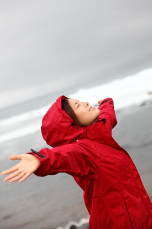raincoat: fall woman in rain happy by ocean. Woman enjoying rainy grey autumn day by the sea. Happy asian caucasian woman outdoor.