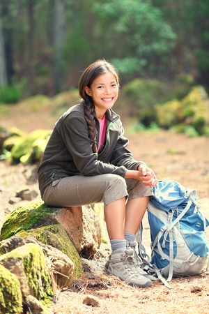 Active healthy woman hiking in beautiful forest. Portrait of happy smiling young woman resting of forest clearing during hike holidays. photo