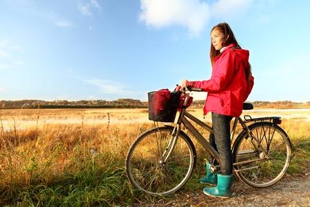 Autumn  fall woman biking on bicycle near field in beautiful landscape. Beautiful young mixed race Caucasian Asian girl. Danish summer landscape near Randers, Denmark. Stock Photo