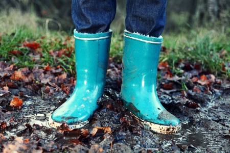 muddy: Fall  Autumn concept - Rain boots in mud puddle. Blue woman rain boots outdoors in action. Stock Photo