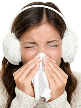 ear muffs: Flu or cold - sneezing woman sick blowing nose. Young woman being cold wearing earmuffs and sweater. Asian Caucasian female model. Stock Photo