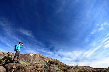 binoculars: hiker in dramatic landscape hiking under deep blue sky looking in binoculars. Young Caucasian man during hike in Mountain landscape on volcano Teide, Tenerife, Canary Islands