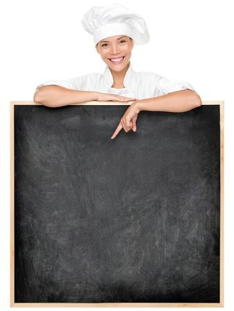 Chef mostrando segno lavagna menù sorridendo felice. Menù lavagna vuota con copia spazio per il testo. Femmina cuoco, panettiere o cucinare isolato su sfondo bianco. Misto asiatico modello razza caucasica femminile.
