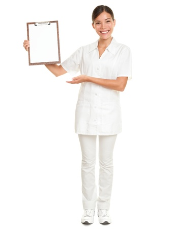 Nurse showing blank clipboard sign - a medical concept. Woman doctor  nurse smiling happy isolated on white background in full body. Mixed race Caucasian  Chinese Asian female model. photo