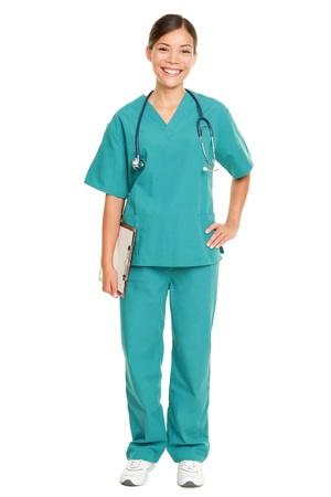 enfermera: De pie o de la enfermera joven m�dico sonriente aislados sobre fondo blanco en todo el cuerpo. Mujer profesional de la medicina en matorrales verdes sonriendo feliz. Mestizos de origen chino modelo femenino de Asia y el C�ucaso. Foto de archivo