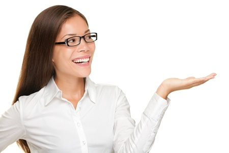 woman pointing: Eyewear woman wearing glasses showing copy space isolated on white background. Beautiful smiling happy mixed race Asian Caucasian female model looking away.