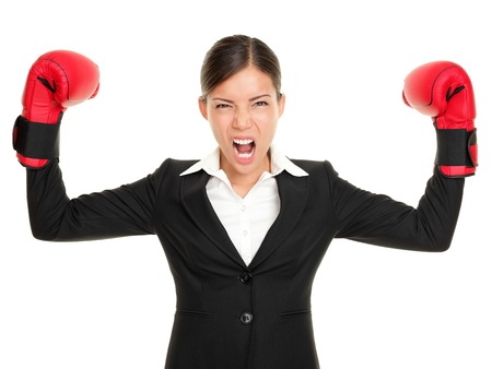 aggressive people: Boxing gloves business woman angry - business concept showing aggressive female businessperson flexing muscles wearing boxing gloves isolated on white background. Mad multiracial businesswoman. Stock Photo