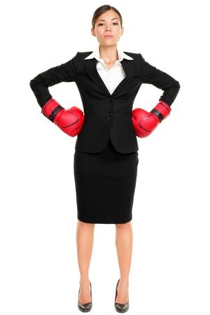mujeres peleando: Ejecutivo concepto de negocios fuerte mujer jefe. Empresaria permanente intimidantes vistiendo guantes de boxeo listos para la competencia. Actitud conf�a por modelo femenino joven mestizo en traje. Foto de archivo