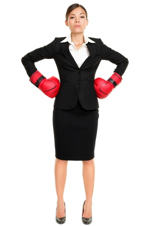 Strong business woman boss executive concept. Businesswoman standing intimidating wearing boxing gloves ready for the competition. Confident attitude by young mixed race female model in suit. photo