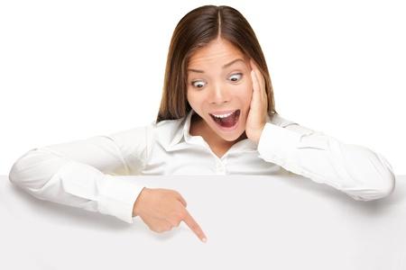 signo de banner de publicidad - mujer excitada señalador mirando hacia abajo a bordo de signo de papel vacío billboard en blanco. Mujer de negocios joven aislada sobre fondo blanco. Foto de archivo