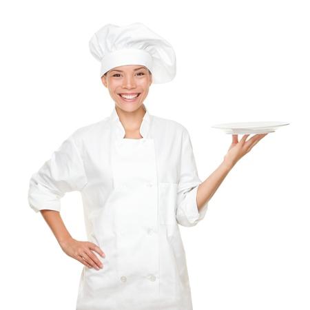 panettiere: Chef mostrando piatto vuoto. Smilng felice ritratto di donna in uniforme e cappello da chef, chef, isolato su sfondo bianco. Asian Caucasica modello. Archivio Fotografico