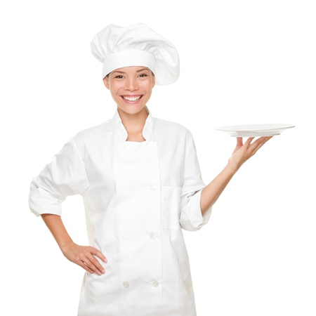 Chef showing empty plate. Happy smilng portrait of female in chef uniform and chef hat isolated on white background. Asian Caucasian woman model.