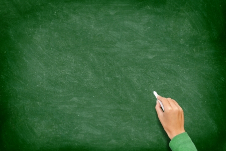primary education: Blank blackboard  chalkboard. Hand writing on green chalk board holding chalk. Great texture for text.