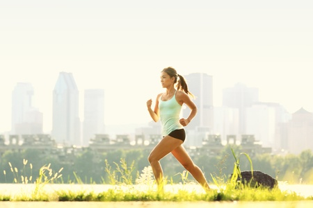 Running in city park. Woman runner outside jogging with Montreal skyline in background Stock Photo
