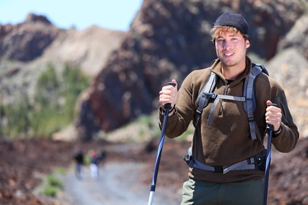 trekker: Adventure hiking man. Portrait in mountain landscape. Caucasian male hiker smiling in nature standing with hiking poles in volcano landscape on Teide, Tenerife, Canary Islands