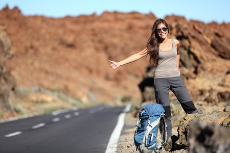 backpackers: Travel woman hitchhiking. Beautiful young female hitchhiker by the road during vacation trip on Volcano Teide, Tenerife, Canary Islands.
