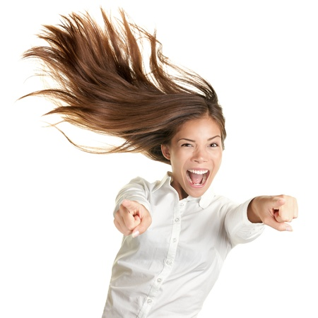 winning business woman: happy crazy excited woman screaming and pointing at camera with wild long hair in the wind. Beautiful ecstatic mixed race Caucasian Asian female model.