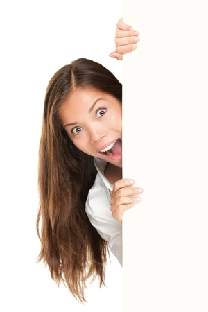 Sign people - woman peeking out from behind billboard paper poster. Excited woman looking surprised at camera. Beautiful brunette with long hair. Asian Caucasian female model isolated on white background Stock Photo
