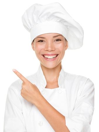 Vrouw chef-kok wijzend  tonen lege lege kopie ruimte geïsoleerd op witte achtergrond. Mooie jonge gemengd ras Aziatische Kaukasische vrouwelijke model glimlachen gelukkig.