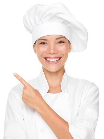 Woman chef pointing  showing empty blank copy space isolated on white background. Beautiful young mixed race Asian Caucasian female model smiling happy. Reklamní fotografie