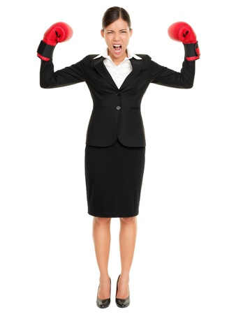 Strong aggressive business winner woman concept. Businesswoman wearing boxing gloves showing flexing muscles standing in full length wearing suit. Caucasian Asian female model isolated on white background. Stock Photo - 10473217