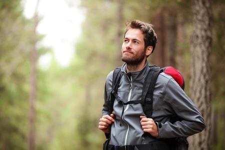 Escursionista - escursioni uomo nella foresta. Escursionista in cerca di sesso maschile di lato a piedi nella foresta. Modello caucasico maschio all'aperto in natura. Archivio Fotografico