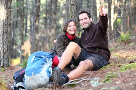 Young happy couple hiking in forest. Smiling couple resting enjoying a break during hike vacations. Caucasian man model. Asian woman model. photo