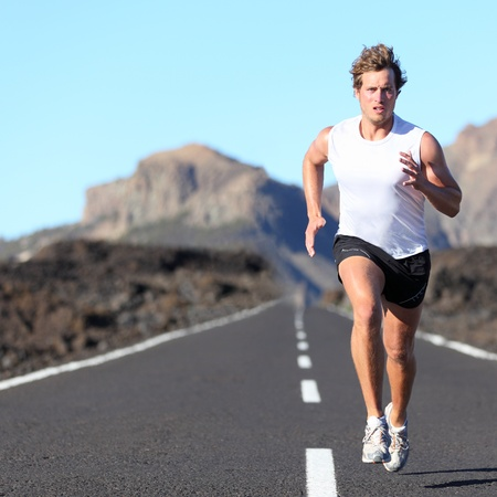 Runner running for Marathon on road in beautiful mountain landscape. Caucasian man jogging outdoors in nature.