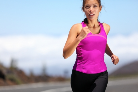 jogging in nature: woman runner training for marathon. Female runner in sporty pink tank top jogging on mountain road. Beautiful young mixed race Asian Caucasian female fitness model outside. Stock Photo