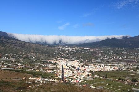 phenomena: La Palma, Canary Islands. Photo shows the rare and famous cloud phenomena where clouds are falling down over the mountain ridge Cumbre Nueva like a waterfall. Also showing city Los Llanos de Aridane Stock Photo