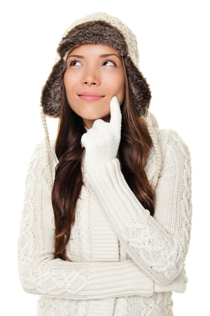 gloves women: Thinking winter woman looking pensive to the side and up wearing warm winter clothing - sweater and tuque wool cap. Happy smiling woman isolated on white background. Asian Caucasian female model. Stock Photo