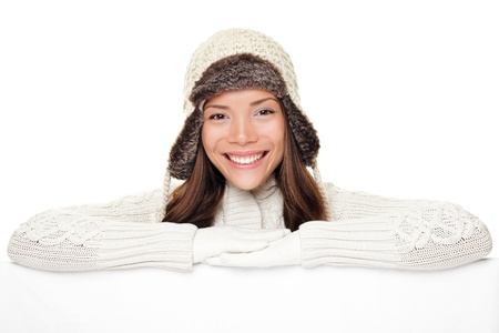 Winter woman sign banner. Cute smiling woman in warm winter sweater and wool cap showing blank white paper poster isolated on white background. photo