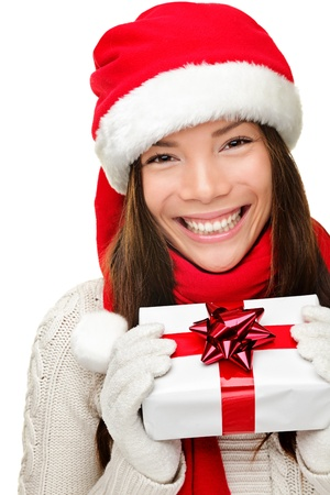 Christmas santa woman holding gift. Smiling happy cute young woman wearing santa hat showing christmas present isolated on white background. Joyful mixed race Asian Caucasian santa girl. photo