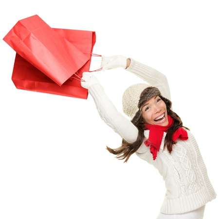Winter and christmas shopping. Woman holding red shopping bags happy, ecstatic and cheering with energy, Isolated on white background.
