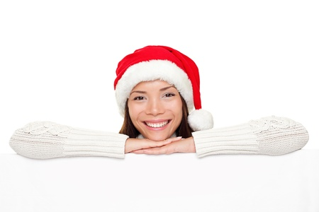 Christmas sign - Santa woman showing blank billboard banner sign smiling happy looking at camera. Beautiful cute mixed race Asian Caucasian female model. photo