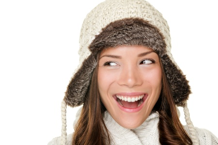 Winter woman looking sideways happy isolated on white background. Closeup portrait of beautiful winter girl wearing warm clothes and winter hat looking to the side. Chinese Asian  Caucasian female model. photo