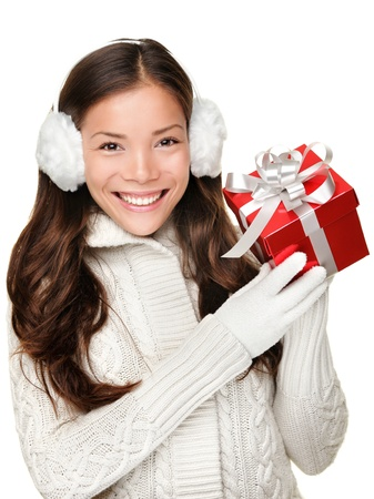 Christmas winter girl holding red present wearing warm sweater and ear muffs. Young beautiful and cute multi-racial woman with lovely smile isolated on white background. Stock Photo