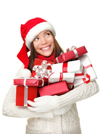 Christmas shopping woman holding gifts smiling happy looking up to the side isolated on white background. Cute Santa girl wearing warm sweater and santa hat holding many christmas presents. Mixed race Asian Caucasian female model.