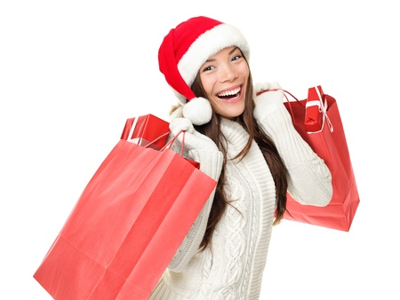 Christmas shopping woman holding shopping bags with gifts. Happy and smiling wearing red santa hat isolated on white background. Mixed race Caucasian  Chinese Asian female model. photo