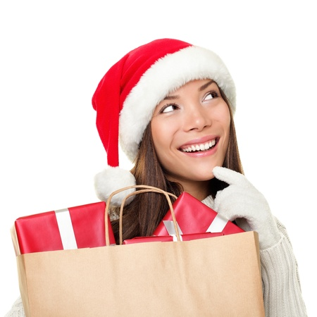 Christmas shopping woman thinking wearing santa hat and holding christmas gifts in shopping bag. Thinking mixed race Chinese Asian  Caucasian female model looking sideways smiling happy isolated on white background.