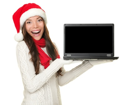 christmas display: Christmas laptop computer woman excited showing monitor screen with copy space. Happy smiling mixed race Chinese Asian  white Caucasian woman wearing santa hat isolated on white background.
