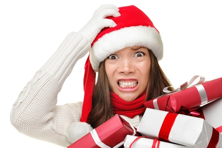 shopper: Christmas stress - busy woman wearing santa hat stressing for christmas shopping holding may christmas gifts in her arms. Funny image of multiracial Asian Caucasian female model isolated on white background.