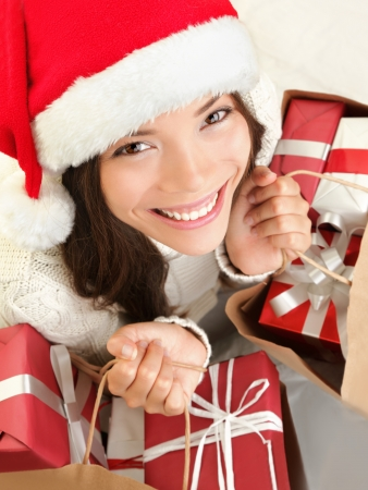 Christmas gift woman shopping wearing santa hat smiling happy. Closeup portrait of cute mixed race Caucasian Asian female model isolated on white background. Stock Photo - 10704091