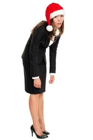 bend over: Christmas business woman tired wearing santa hat standing bored bending over. Christmas business concept of businesswoman stressed and exhausted isolated in full body on white background. Asian Caucasian female model. Stock Photo