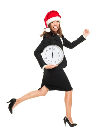 Christmas busy concept. business woman running late busy from work for holidays. Full body portrait of asian caucasian businesswoman wearing santa hat running with clock. Isolated on white background. photo
