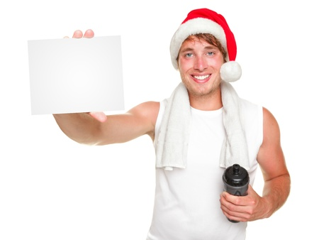 new years resolution: Christmas santa exercise man showing white gift  business card for holiday message. Fit young man wearing santa hat Isolated on white background.