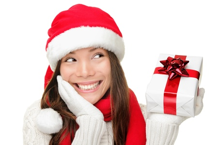 Santa girl holding christmas gift. Young happy woman in santa hat looking sideways showing Christmas present isolated on white background. Beautiful cute young santa woman. Stock Photo